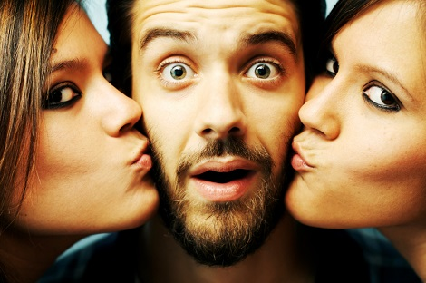 Lucky guy gets a kiss from two cute twins.