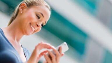 Ragazza sorride leggendo un messaggio appena ricevuto
